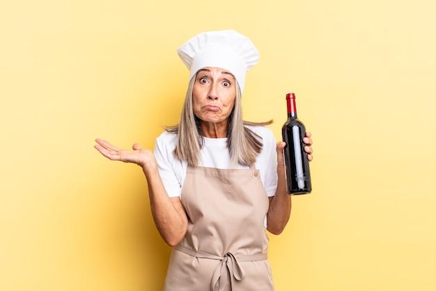 Chef-kokvrouw van middelbare leeftijd die zich verward en verward voelt, twijfelt, weegt of verschillende opties kiest met een grappige uitdrukking die een wijnfles vasthoudt