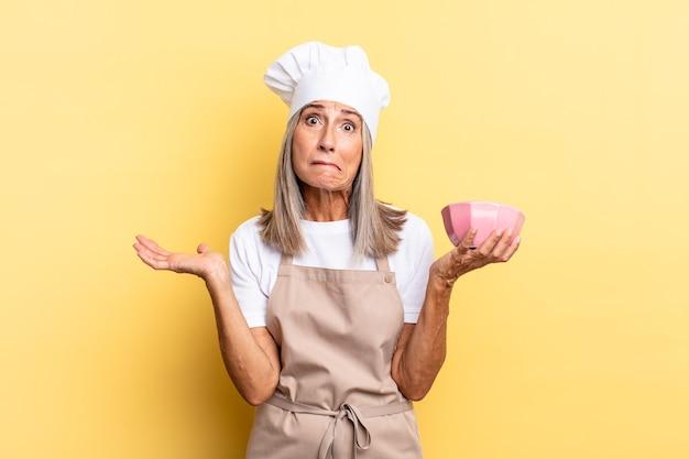 Chef-kokvrouw van middelbare leeftijd die zich verward en verward voelt, twijfelt, weegt of verschillende opties kiest met grappige uitdrukking en een lege pot vasthoudt