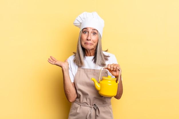 Chef-kokvrouw van middelbare leeftijd die zich verward en verward voelt, twijfelt, weegt of verschillende opties kiest met grappige uitdrukking en een theepot vasthoudt
