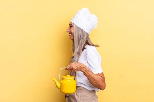 Chef-kokvrouw van middelbare leeftijd in profielweergave die ruimte vooruit wil kopiëren, denken, fantaseren of dagdromen en een theepot vasthouden