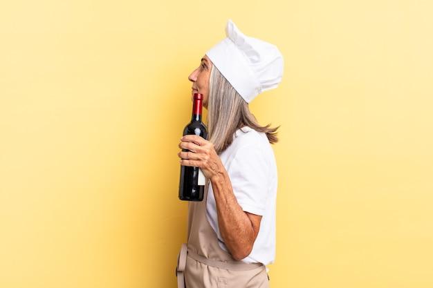 Chef-kokvrouw van middelbare leeftijd in profielweergave die ruimte vooruit wil kopiëren, denken, fantaseren of dagdromen met een wijnfles