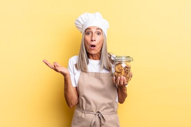 Chef-kokvrouw van middelbare leeftijd met open mond en verbaasd, geschokt en verbaasd met een ongelooflijke verrassing met koekjes