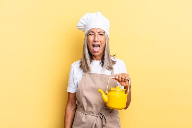 Chef-kokvrouw van middelbare leeftijd met vrolijke, zorgeloze, rebelse houding, grappen maken en tong uitsteken, plezier hebben en een theepot vasthouden