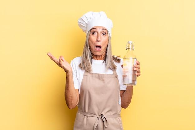 Chef-kokvrouw van middelbare leeftijd voelt zich extreem geschokt en verrast, angstig en in paniek, met een gestresste en geschokte blik met een waterfles Premium Foto