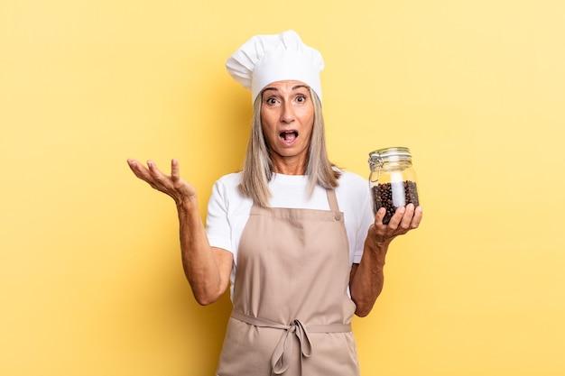 Chef-kokvrouw van middelbare leeftijd voelt zich extreem geschokt en verrast, angstig en in paniek, met een gestresste en geschokte blik met koffiebonen