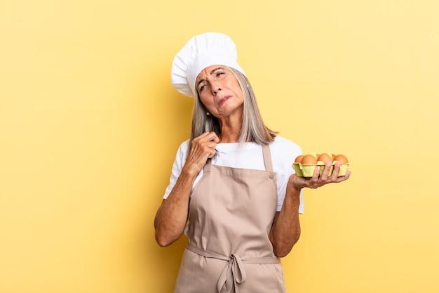 Chef-kokvrouw van middelbare leeftijd voelt zich gestrest, angstig, moe en gefrustreerd, trekt aan de nek van het shirt, ziet er gefrustreerd uit met een probleem met het vasthouden van een eierdoos