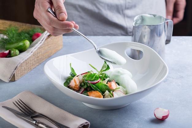 Chef maakt de kooksalade af en voegt met een witte saus toe aan rode vis en groenten.