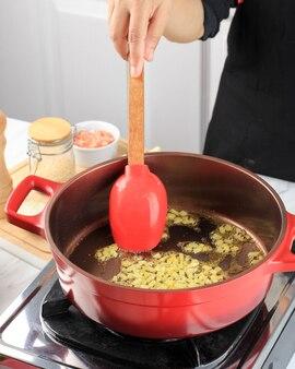 Chef roert witte gesnipperde uien die gebakken worden in een rode gietijzeren nederlandse oven