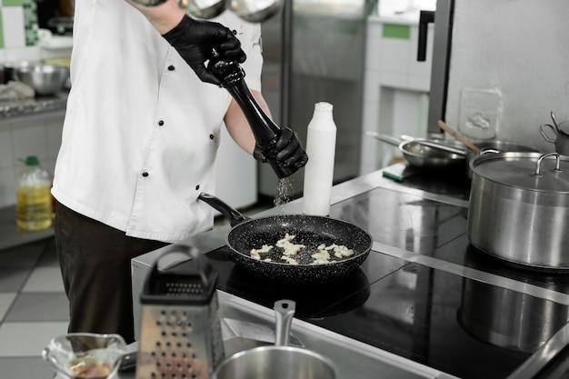 Chef's handen in een tuniek die zout of peper toevoegt aan een gerecht bij het bakken in een pan