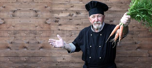 Chef senior in uniform met groenten in handen Premium Foto