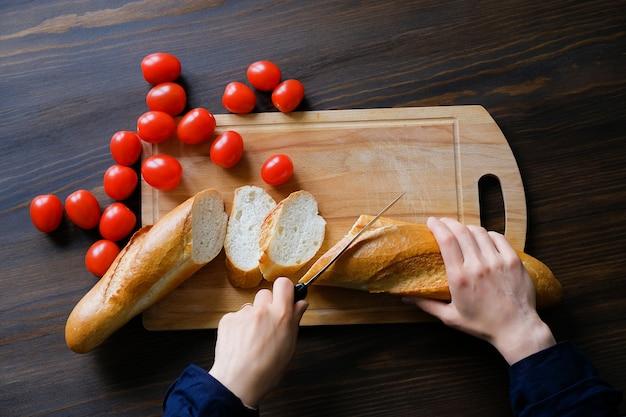 Chef sneed met een mes een wit brood