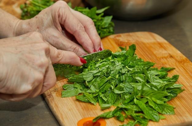 Chef snijdt basilicum volgens het recept voor koken op een houten bord in de keuken