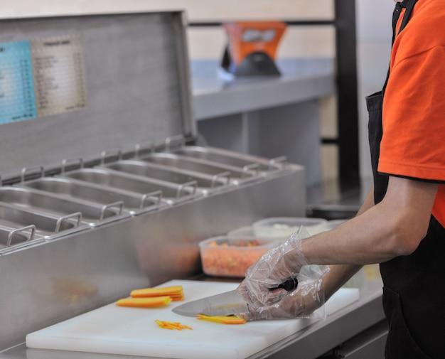 Chef snijdt de groenten in fastfoodrestaurant cook in de keuken van het restaurant