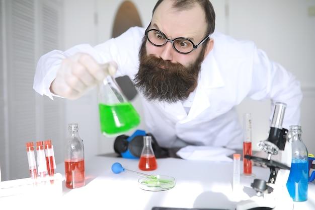 Chemicus gek. een gekke wetenschapper voert experimenten uit in een wetenschappelijk laboratorium. doet onderzoek met behulp van een microscoop.