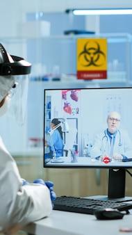 Chemicus in ppe-pak luisteren professionele arts op videogesprek, bespreken tijdens virtuele vergadering in onderzoekslaboratorium. artsen die hightech gebruiken voor onderzoek naar behandeling tegen covid19-virus