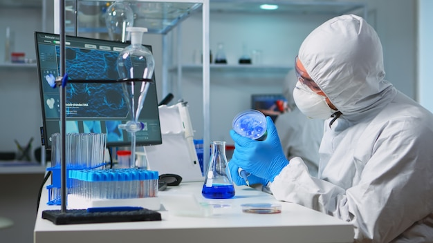 Chemicus in ppe-pak met micropipet voor het vullen van reageerbuizen in modern uitgerust laboratorium. team van wetenschappers die de evolutie van het virus onderzoeken met behulp van hightech voor de ontwikkeling van vaccins tegen covid19