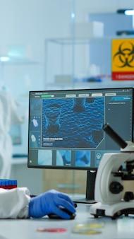 Chemicus in ppe-pak typen op pc die vaccinontwikkeling controleert in modern uitgerust laboratorium. arts die werkt met verschillende bacteriën, weefsel- en bloedmonsters, farmaceutisch onderzoek naar antibiotica