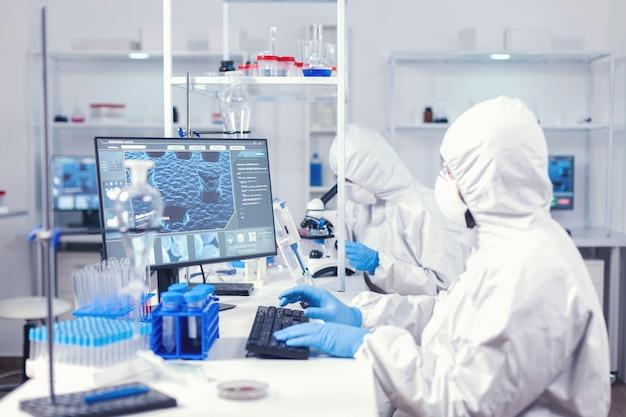 Chemicus in ppe-pak typen op toetsenbord die virusontwikkeling controleert in uitgerust laboratorium. medisch ingenieur die computer gebruikt tijdens wereldwijde pandemie met coronavirus gekleed in overall.