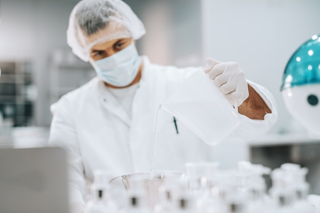 Chemicus in steriel uniform gietend water in cruse. selectieve aandacht bij de hand