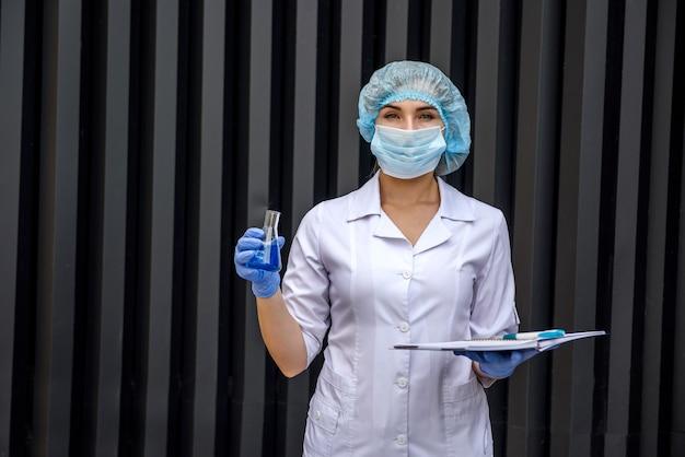 Chemicus met reageerbuizen poseren in laboratorium tijdens het maken van wetenschappelijk experiment