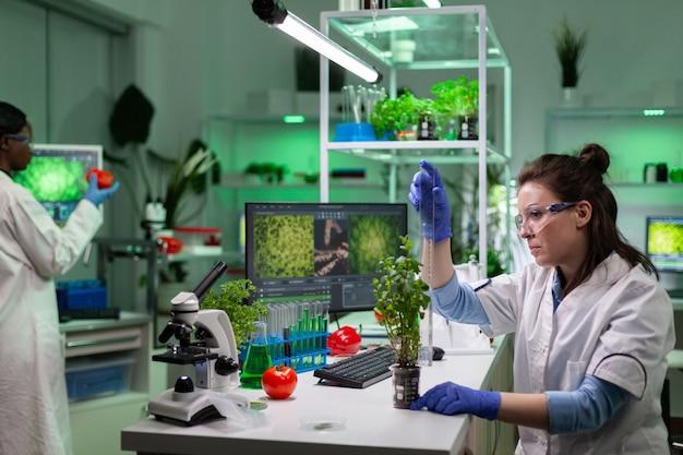 Chemicus onderzoeker vrouw meten groene jonge boom met behulp van liniaal