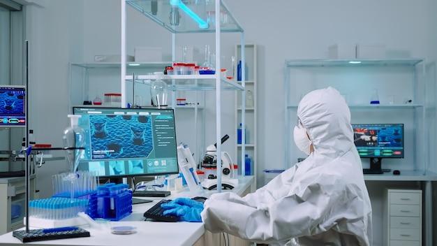 Chemicus typt op pc en collega analyseert microscoopglaasjes in uitgerust laboratorium. team van wetenschappers die de evolutie van vaccins onderzoeken met behulp van hightech voor onderzoek naar behandeling tegen het covid19-virus