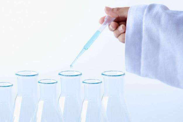Chemicushand die een medische druppelaar gevuld houden