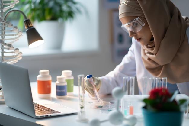 Chemisch laboratorium. vrouw met hijab die in het chemisch laboratorium werkt en chemische middelen bestudeert