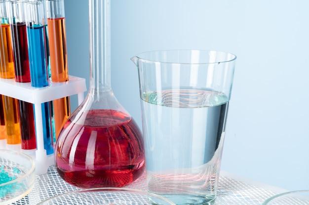 Chemisch laboratoriumglaswerk met verschillende gekleurde vloeistoffen op tafel