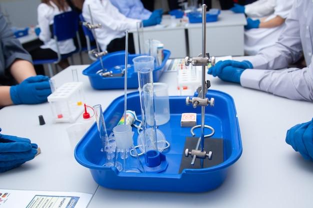 Chemische ervaring close-up. gehandschoende handen houden een flesje vloeistof vast. schoolexperimenten. scheikunde lessen. laboratorium. hoge kwaliteit foto
