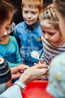 Chemische show voor kinderen. professor voerde chemische experimenten uit met vloeibare stikstof op het verjaardagsmeisje.