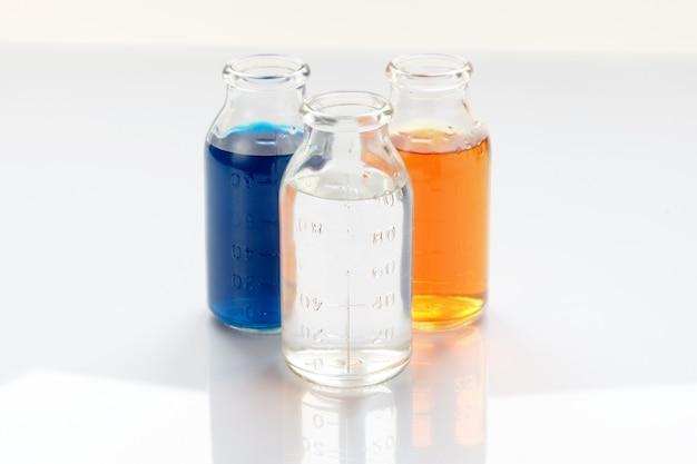 Chemische vaten met kleurrijke vloeistoffen op witte achtergrond