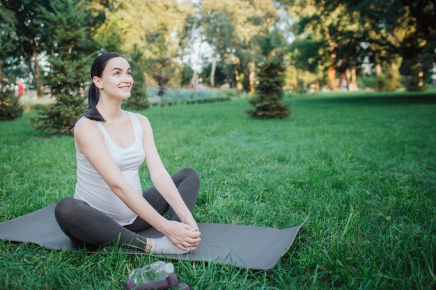 Cherful aardige jonge vrouw het uitrekken zich benen op yogapartner buiten in park. ze glimlacht en houdt handen op voeten.