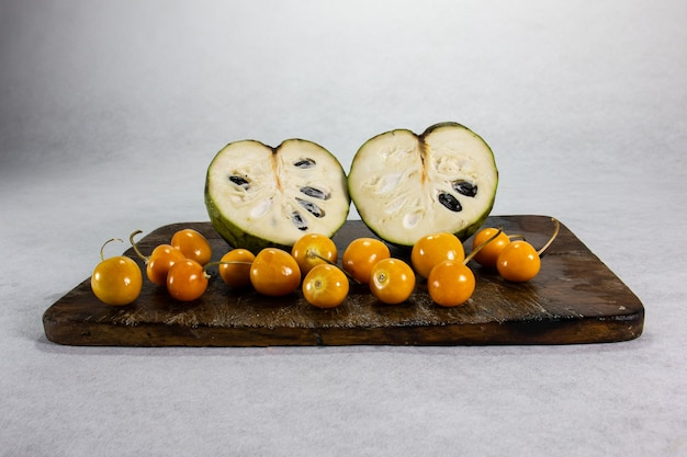 Cherimoya y uchuva aguaymanto uvilla exotisch peruviaans latijns amerikaans fruit zit op een bruin houten bord en een witte achtergrond met schaduwen