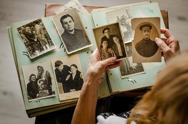 Cherkasy / oekraïne - 12 december 2019: vrouwelijke handen houden en oude foto van haar familieleden. vintage fotoalbum met foto's. familie en levenswaarden concept.