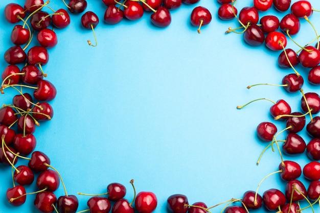 Cherry bessen grens op een blauwe achtergrond bovenaanzicht