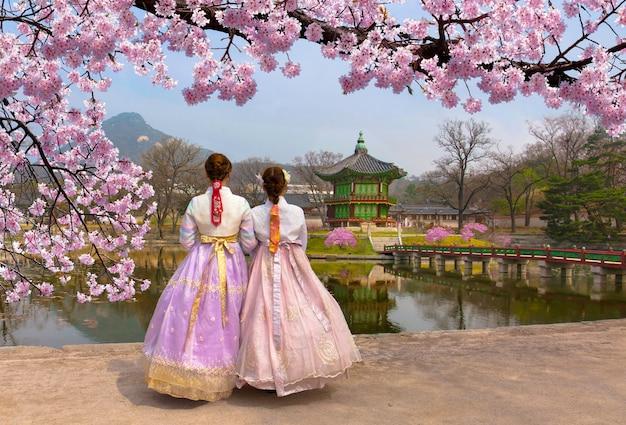 Cherry blossom in het voorjaar met koreaanse nationale klederdracht in gyeongbokgung palace seoul, zuid-korea.