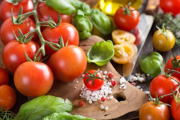 Cherry tomaten, basilicum en olijfolie op een houten tafel