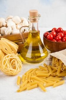 Cherry tomaten met olijfolie, champignons en rauwe pasta's op het marmer.