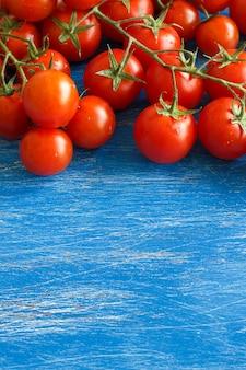 Cherry tomaten op de oude blauwe houten tafel close-up