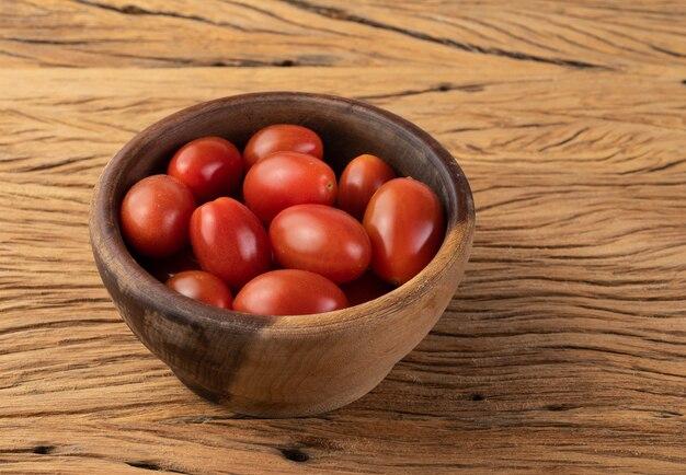 Cherry tomaten op een kom over houten tafel.