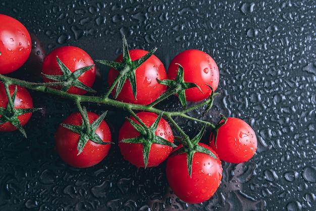 Cherry tomaten vallende waterdruppels geïsoleerd op zwarte ruimte