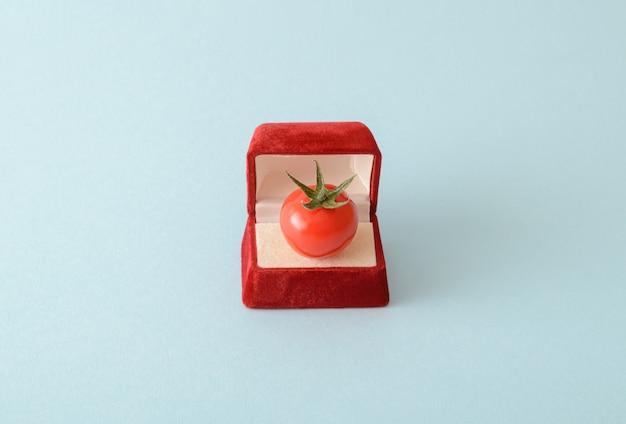 Cherrytomaat in een verlovingsringdoos. op een crèmekleurige achtergrond. het concept van huwelijk en verloving. romantisch levensstijl idee. eenvoudige compositie.