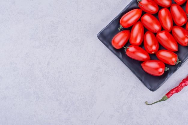 Cherrytomaatjes en rode chilipeper in een zwarte schotel.