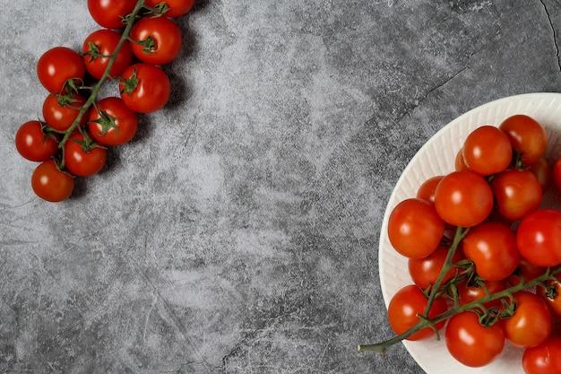 Cherrytomaatjes over grijze achtergrond aan de rechterkant met witte plaat