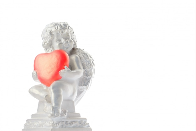 Cherubijnstandbeeld op witte oppervlakte wordt geïsoleerd, engel houdt het hart, liefde die