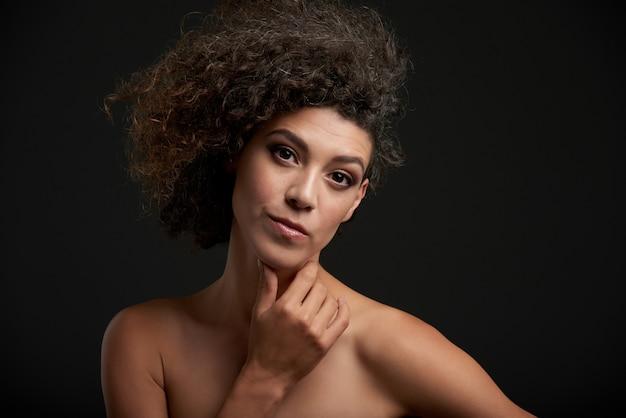 Chestupportret van een krullende brunette