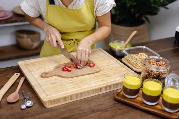 Chia pudding maken. vrouw gesneden aardbei op een houten bord.