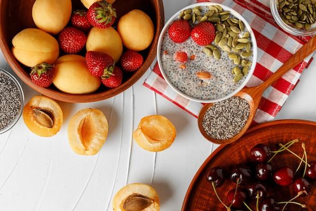 Chia pudding met aardbeien en pompoenpitten op houten tafel met abrikozen