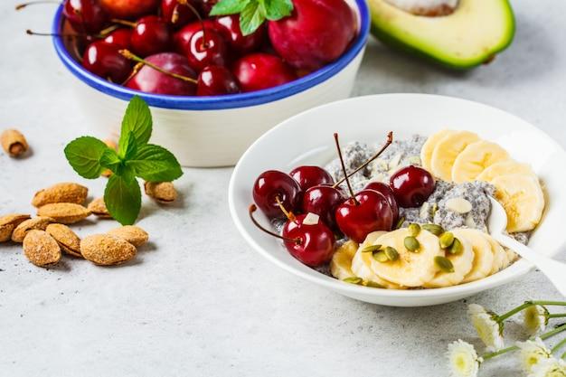 Chia pudding met banaan, kers en noten in witte plaat.